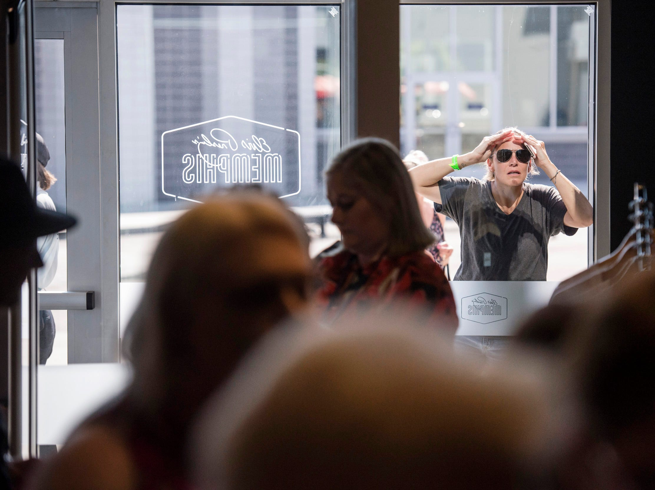 "August 10, 2018 - A woman looks through the window at a private ribbon-cutting event for the new exhibit ""Lisa Marie: Growing Up Presley"" at Elvis Presley's Memphis entertainment complex."