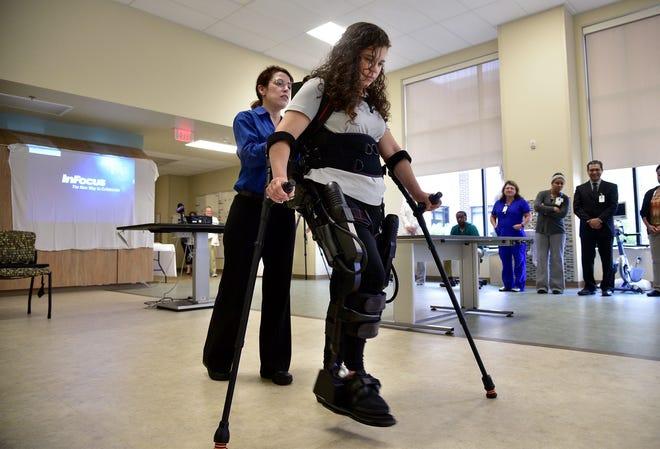August 9, 2018 - Hillary Barrera demonstrates the EksoGT robotic exoskeleton at Baptist Memorial Rehabilitation Hospital on Thursday evening with physical therapist Leslie VanHiel.