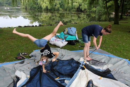 Sarah Baumgartener of Iron River, Michigan, assembles tent poles while daughter Lydia practices gymnastics next to Lake Evinrude on Aug. 9 during the Milwaukee County Zoo's Snooze at the Zoo.  The zoo sold out 103 camping sites for each of the event's four nights. Campers would set up at 5 p.m. for a night of special events, then be packed up by 9 in the morning.
