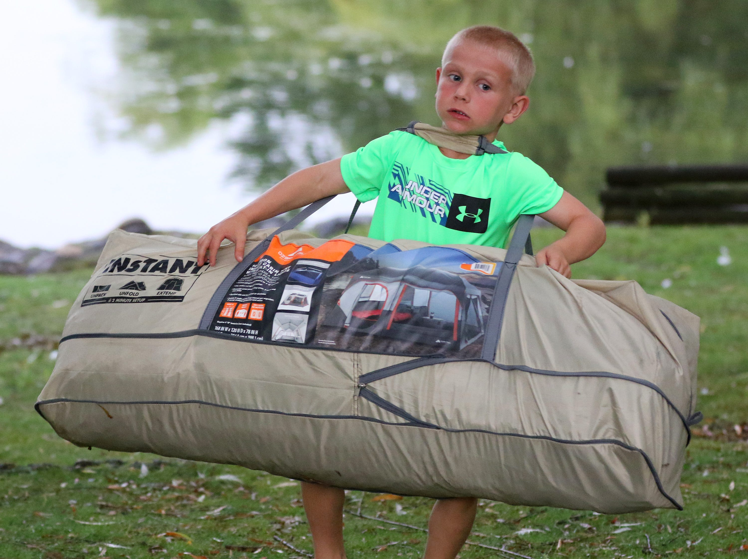 Gavin Lovejoy of Delafield tries to muscle the family's tent into place next to Lake Evinrude on Aug. 9 during the Milwaukee County Zoo's Snooze at the Zoo.