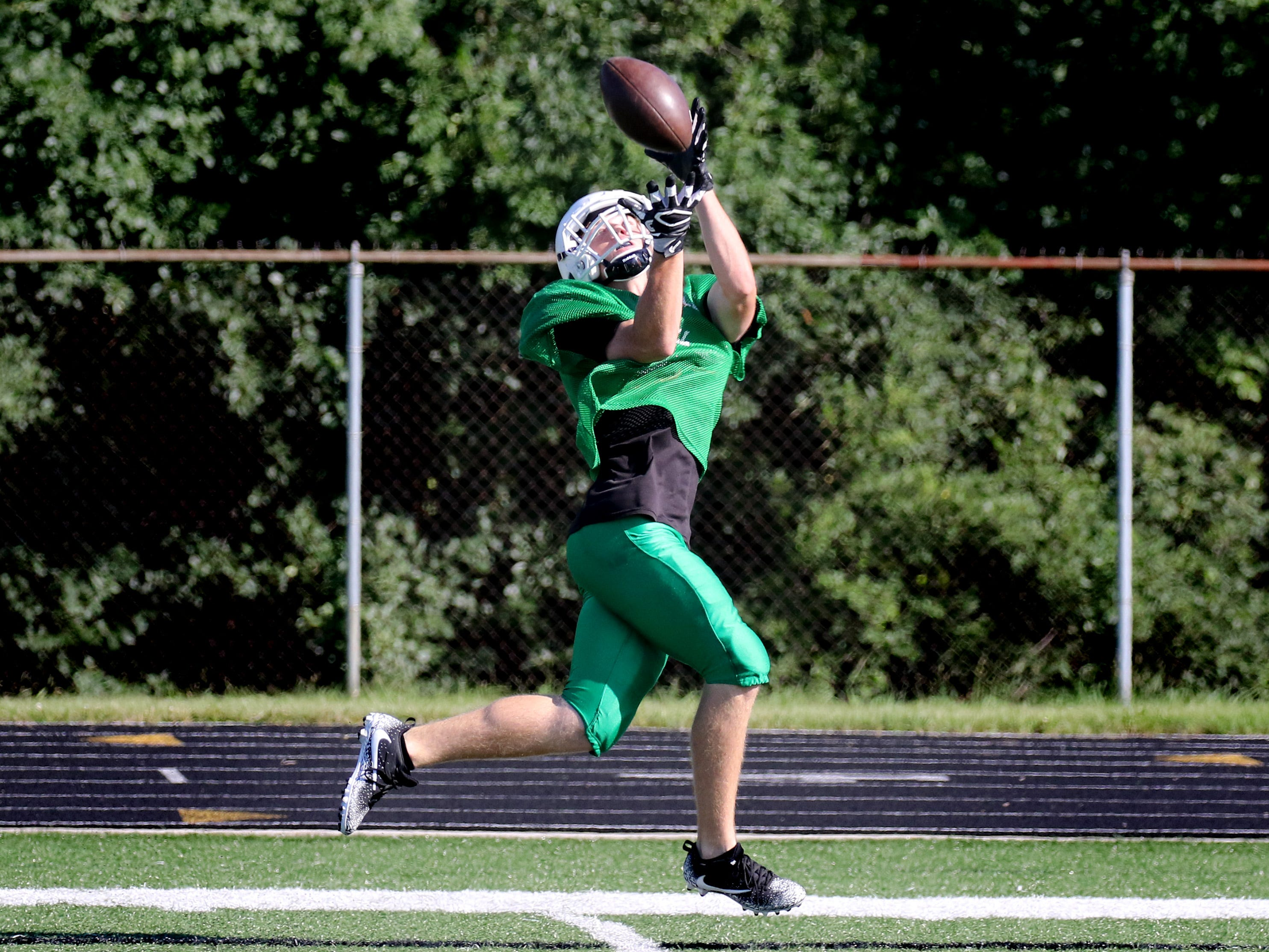 A Greendale receiver heads for a touchdown untouched by Milwaukee Riverside defenders during a scrimmage at Greendale High School on Aug. 10.