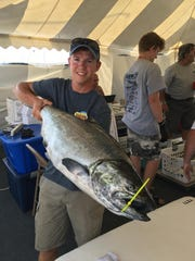 Andrew Becker, a first mate with Jack's Charter Service in Milwaukee, shows a 25.4-pound chinook salmon caught during the 2018 Brew City Salmon Tournament.