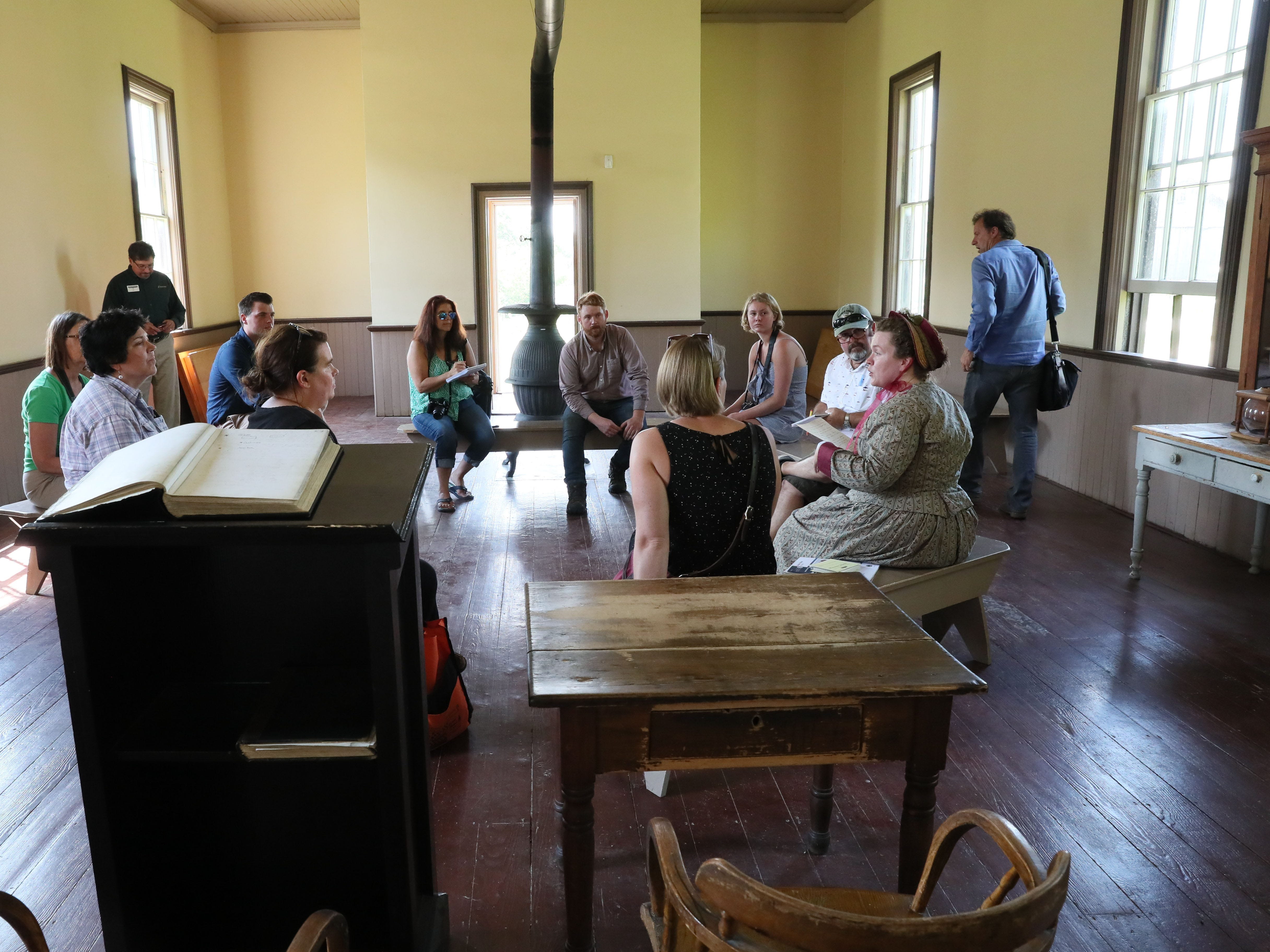 "Anna Altschwager, assistant director of guest experience at Old World Wisconsin, leads a discussion in Harmony Town Hall that's part a 90-minute immersive experience called ""The Wisconsin Journey."" The new program focuses on the immigrant journey to Wisconsin."