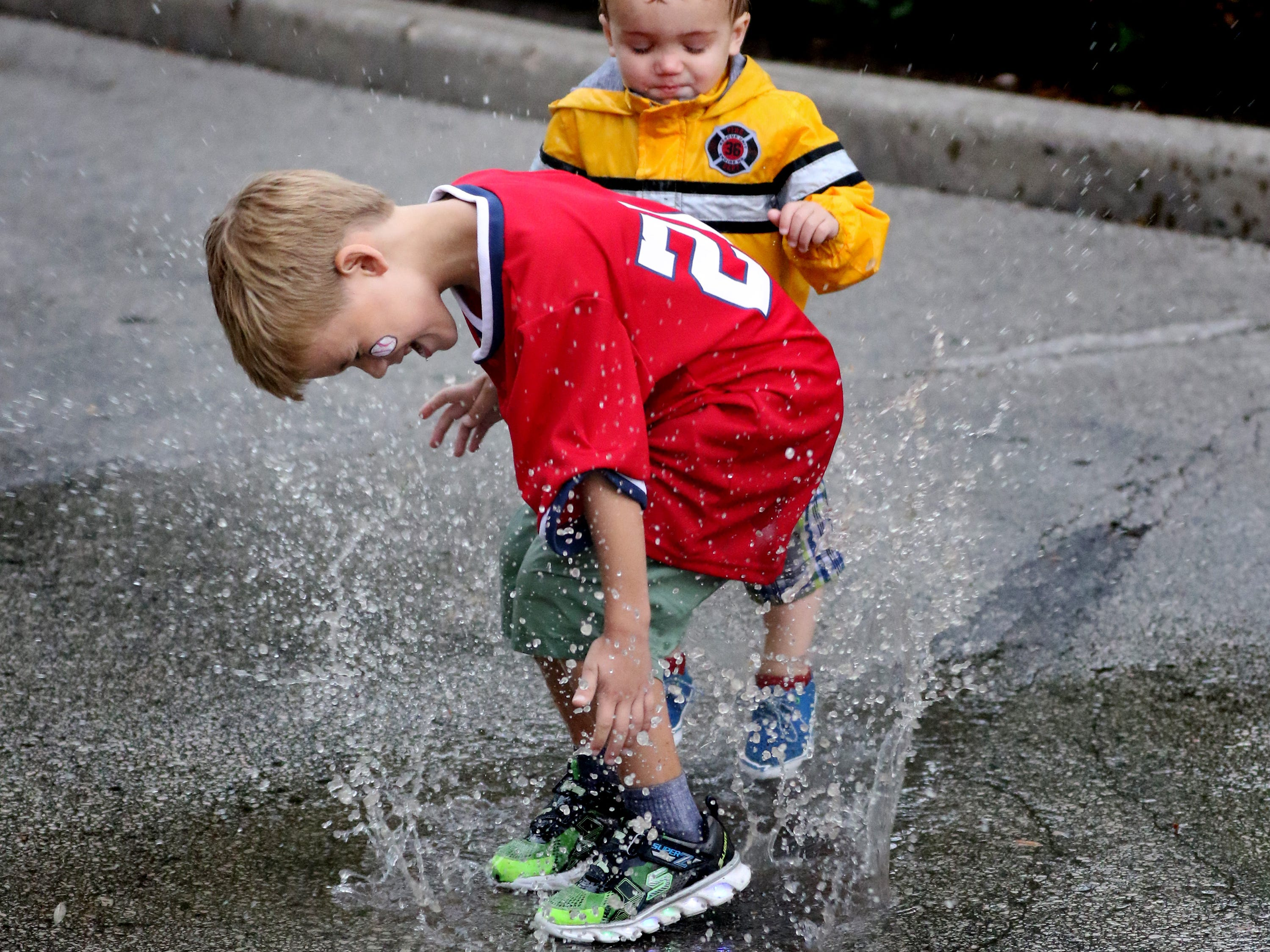 Teddy (front) and Calvin Davis find s puddle to play in on Aug. 9 during the Milwaukee County Zoo's Snooze at the Zoo that sold out 103 camping sites for each of the event's four nights. Campers would set up at 5 p.m. for a night of special events, then be packed up by 9 in the morning.
