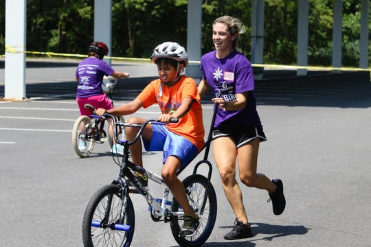 Volunteer Kaitlin Listro guides Vithun Sivaraj, 10, on learning how to ride a bike during the iCan Bike program at Randolph High School on August 10, 2018.