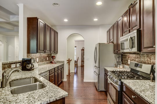The kitchen of 318 Birkshire Place features granite countertops, a backsplash and stainless appliances. The home has 3,489 square feet of space.