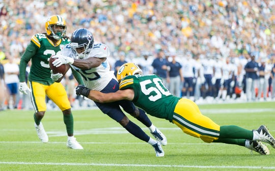 Titans wide receiver Darius Jennings (15) dives for a touchdown as Packers linebacker Blake Martinez (50) tries to stop him during the first quarter Thursday.