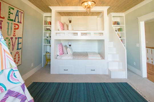 This built-in bunk bed unit features extra storage and stairs leading to the top bunk with bookcases on either side of the beds.