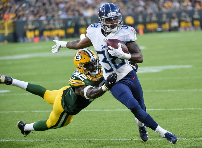 Aug 9, 2018; Green Bay, WI, USA; Tennessee Titans running back Akrum Wadley (38) breaks a tackle by Green Bay Packers linebacker Oren Burks (42) for a first down in the second quarter at Lambeau Field.