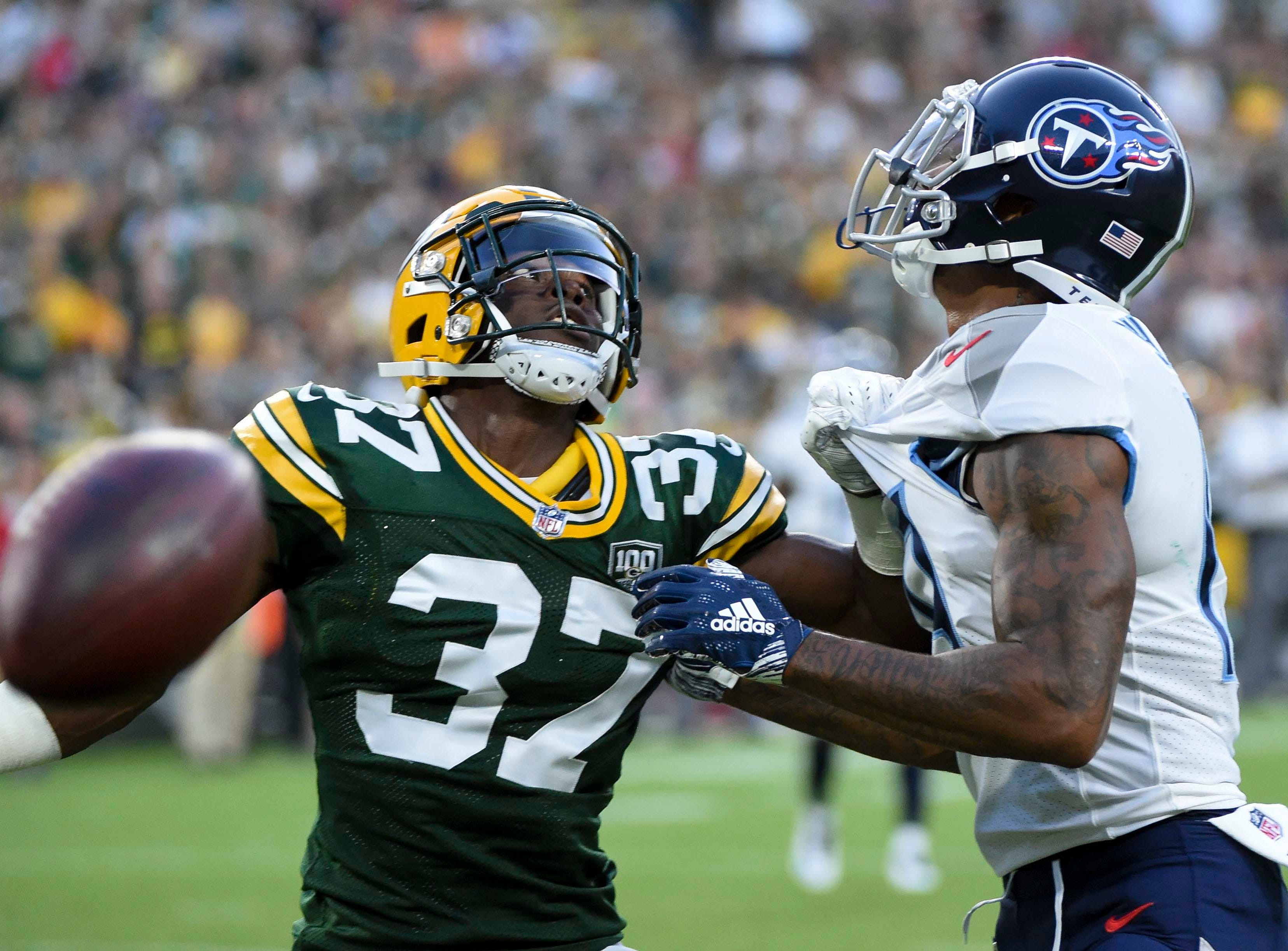 Aug 9, 2018; Green Bay, WI, USA; Green Bay Packers cornerback Josh Jackson (37) keeps Tennessee Titans wide receiver Tajae Sharpe (19) away from a pass in the second quarter at Lambeau Field.