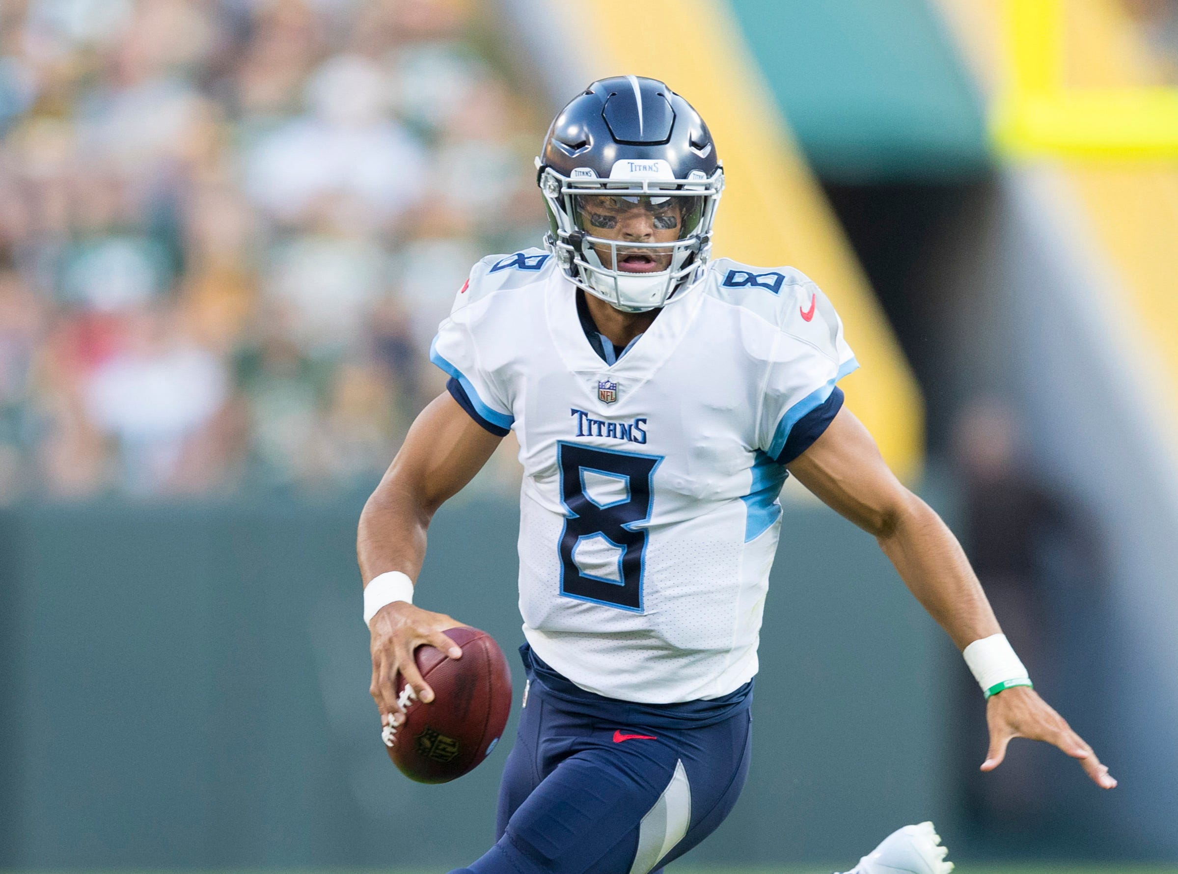 Aug 9, 2018; Green Bay, WI, USA; Tennessee Titans quarterback Marcus Mariota (8) scrambles with the football during the first quarter against the Green Bay Packers at Lambeau Field. Mandatory Credit: Jeff Hanisch-USA TODAY Sports