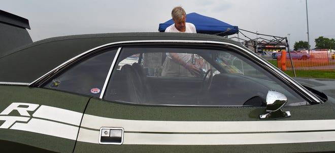 Dan Jones, of Cincinnati, dries off his 1971 Dodge Challenger R/T after a bout of heavy rain during Mopar Nationals weekend at National Trail Raceway.