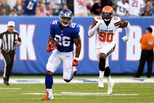 New York Giants running back Saquon Barkley (26) rushes with the ball in the first play of the game. The New York Giants face the Cleveland Browns in a preseason game in East Rutherford, NJ on Thursday, August 9, 2018.