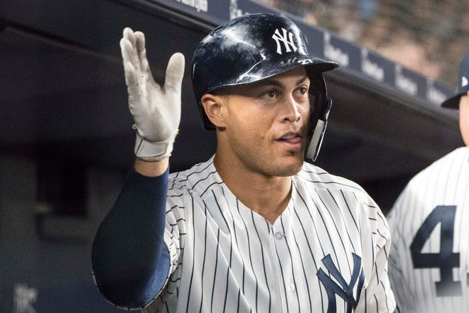 Aug 9, 2018; Bronx, NY, USA; Teammates congratulate New York Yankees right fielder Giancarlo Stanton (27) in the dugout after hitting a home run during the fifth inning of the game against the Texas Rangers at Yankee Stadium.