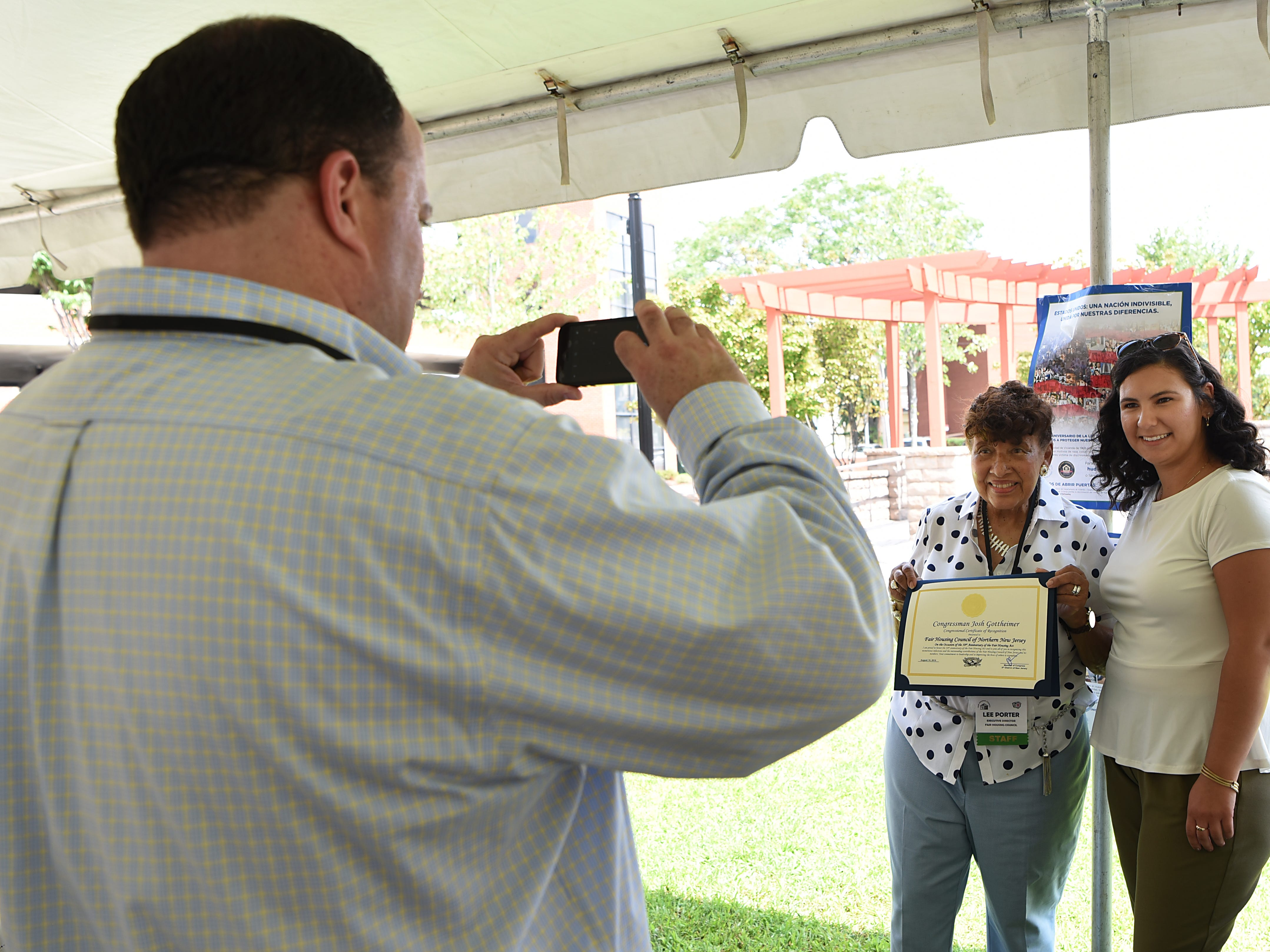 David Whritenour takes a photo of Lee Porter and Kasia Was. The Fair Housing Council of Northern New Jersey holds a picnic in Hackensack on Friday August 10, 2018.