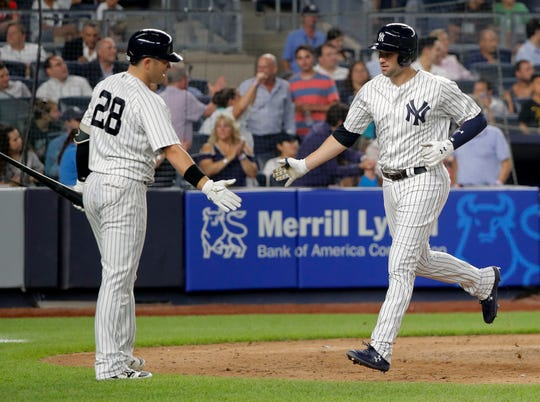 New York Yankees' Neil Walker, right, is congratulated by Austin Romine (28) after hitting a solo home run against the Texas Rangers during the sixth inning of a baseball game, Thursday, Aug. 9, 2018, in New York.