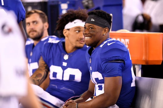 New York Giants running back Saquon Barkley (26) smiles on the bench. The New York Giants face the Cleveland Browns in a preseason game in East Rutherford, NJ on Thursday, August 9, 2018.