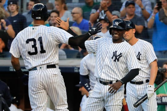 New York Yankees' Aaron Hicks (31) is congratulated by Didi Gregorius after hitting a two-run home run against the Texas Rangers during the first inning of a baseball game, Thursday, Aug. 9, 2018, in New York.