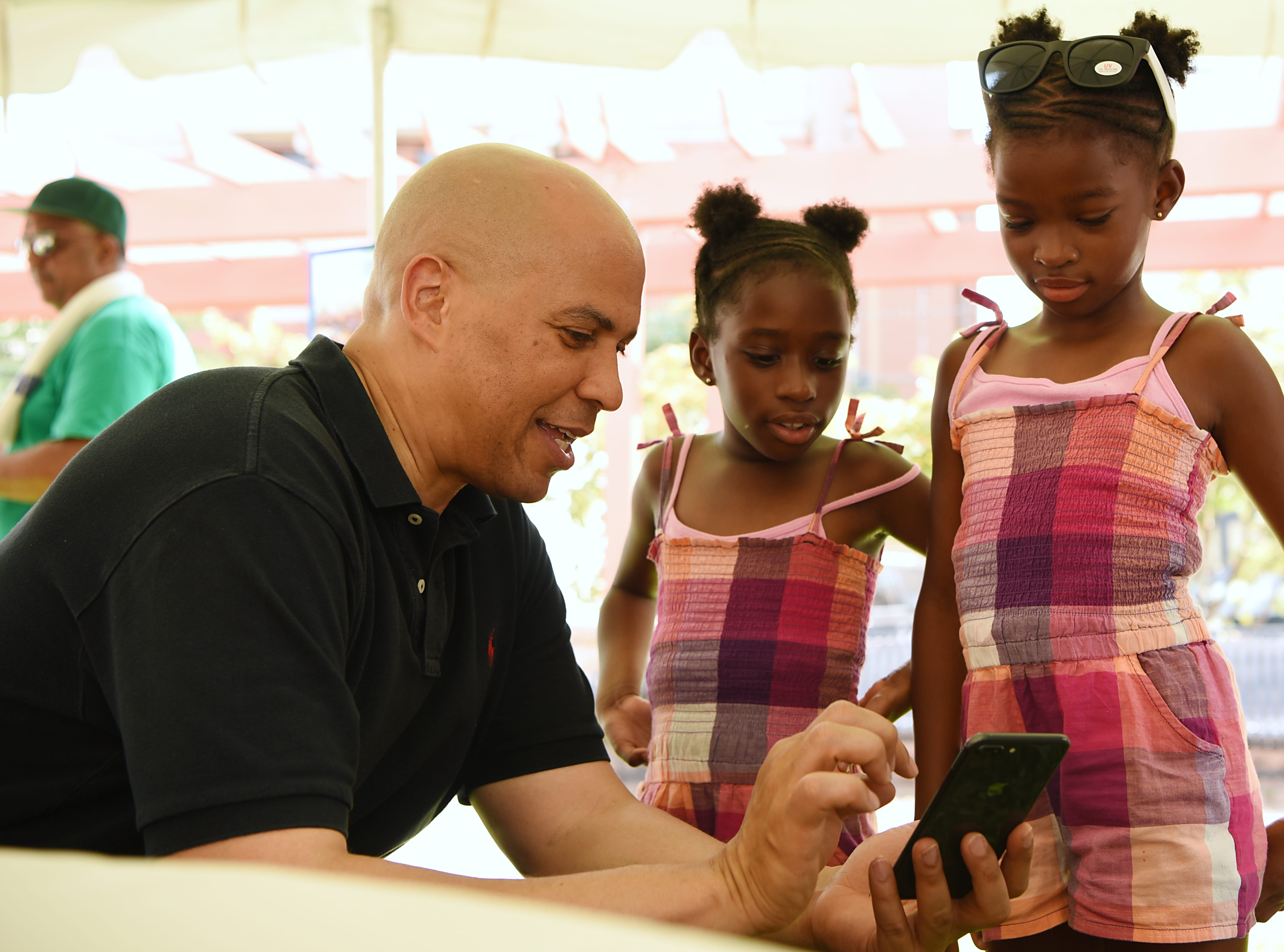 Senator Cory Booker get approval from Oliva and Camille, seven year old twins from Teaneck, after taking a selfie during the Fair Housing Council of Northern New Jersey picnic in Hackensack on Friday August 10, 2018.