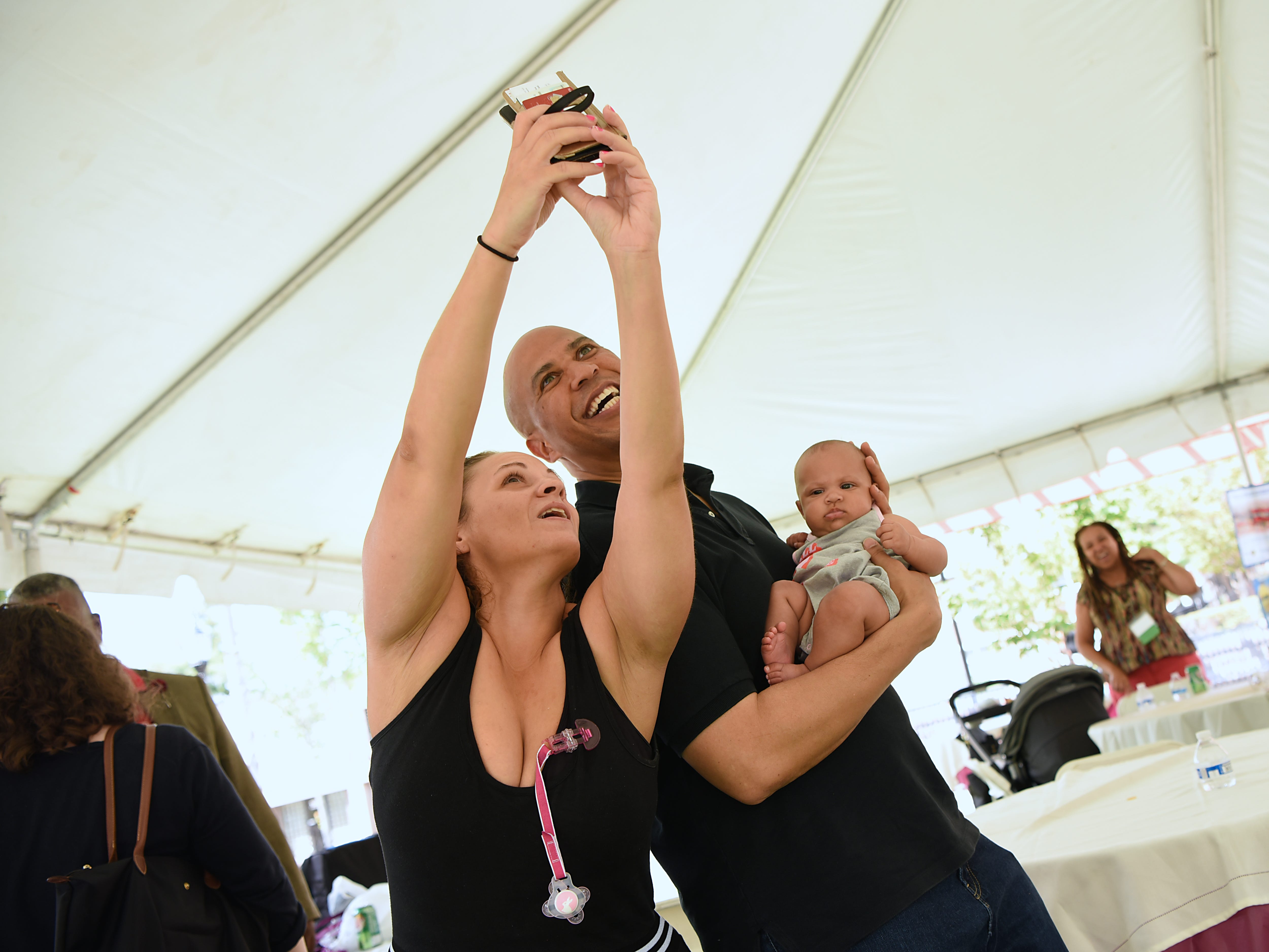Barbara Castellano takes a selfie with Senator Cory Booker as he holds her baby, Jordyn Castellano, during the Fair Housing Council of Northern New Jersey picnic in Hackensack on Friday August 10, 2018.