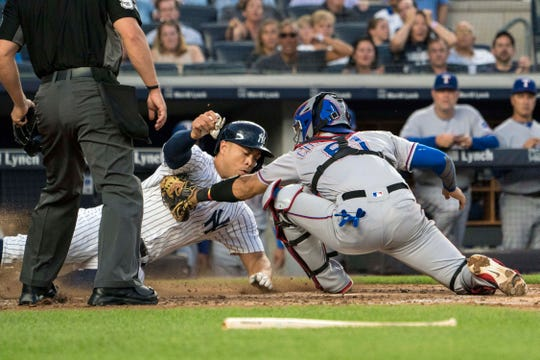 Aug 9, 2018; Bronx, NY, USA; Texas Rangers catcher Robinson Chirinos (61) tags out New York Yankees right fielder Giancarlo Stanton (27) during the third inning of the game at Yankee Stadium.