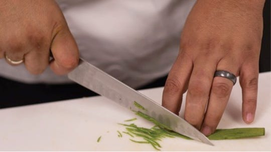 Chef Andres Padilla chops a green onion while preparing a meal during HRTM's Chef Artist Dinner.