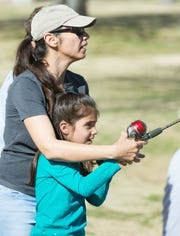 Liz Moreno teaches her daughter Ally Moreno, 7, to cast her line during a free fishing clinic at Alumni Pond in March.