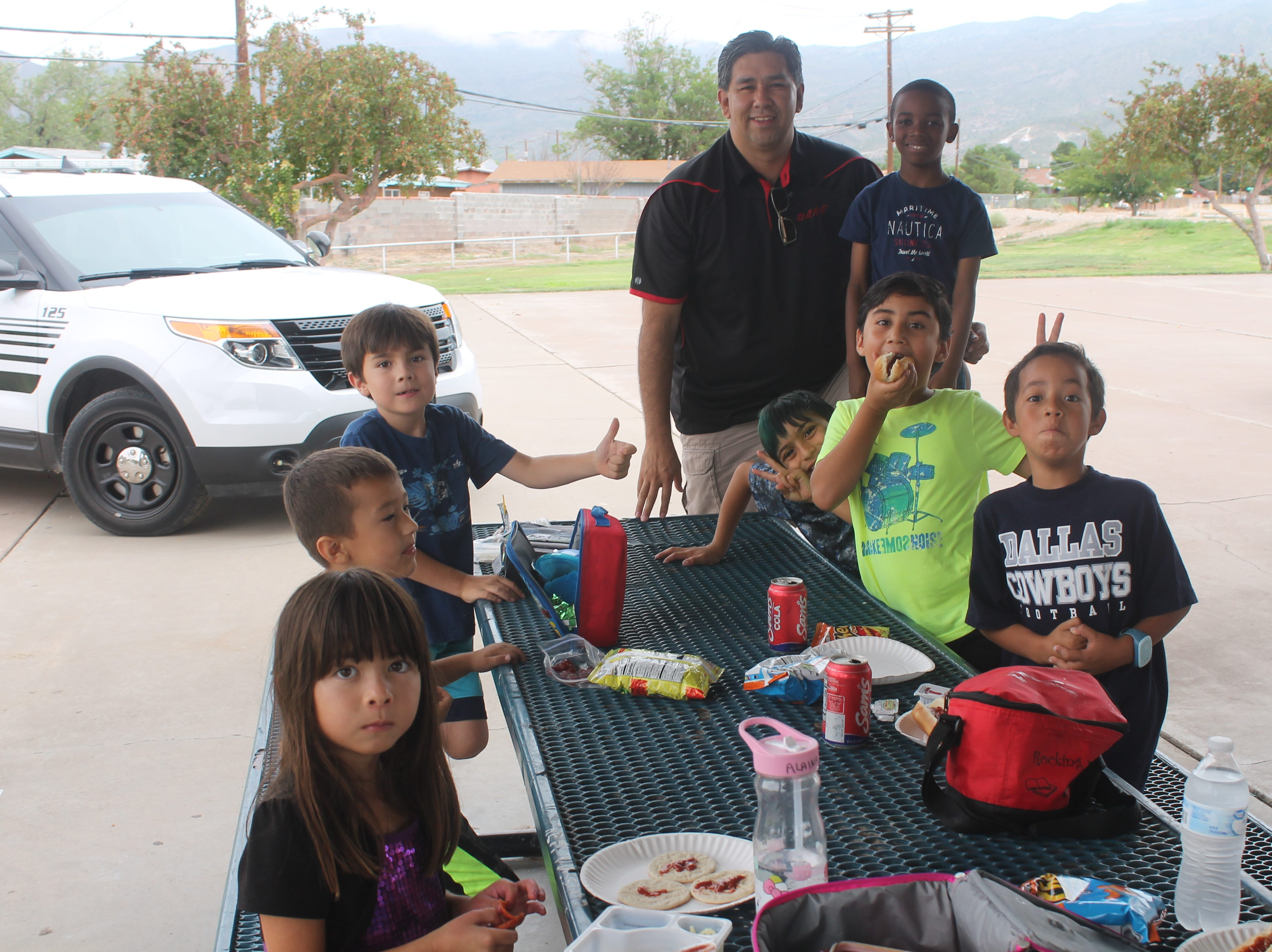 APD officer James McGuinn poses with some Boys and Girls club campers as they chow down.