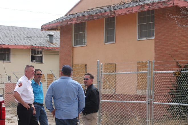 Alamogordo Fire Chief Jim LeClair, Engineering Manager Bob Johnson, a construction supervisor, and Assistant City Manager Brian Cesar discuss plans to begin asbestos abatement at the abandoned Sahara Apartment complex on Wednesday.