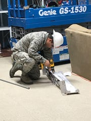 An Airman from the 49th Civil Engineer Squadron repairs a light fixture during the renovation of building 232.