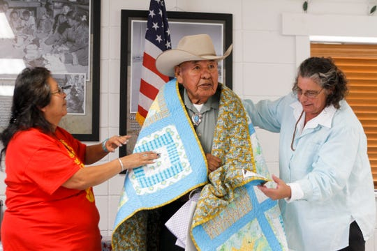 Etta Arviso, left, and Marsha Monestersky, right, honor Navy veteran Harold Lope with a quilt Friday during a ceremony hosted by the Quilts of Valor Foundation at the Farmington Indian Center.