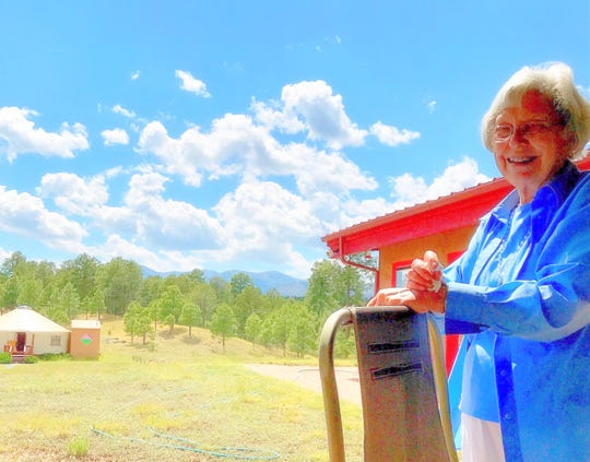 Healing center founder Barbara Mader smiles with the yurt in the distance.