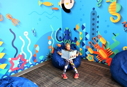 Eight year old Adeline Rust reads 'The Lion, the Witch and the Wardrobe', surrounded by the freshly designed mural, in the new library at Sierra Vista Primary School on White Mountain Drive.