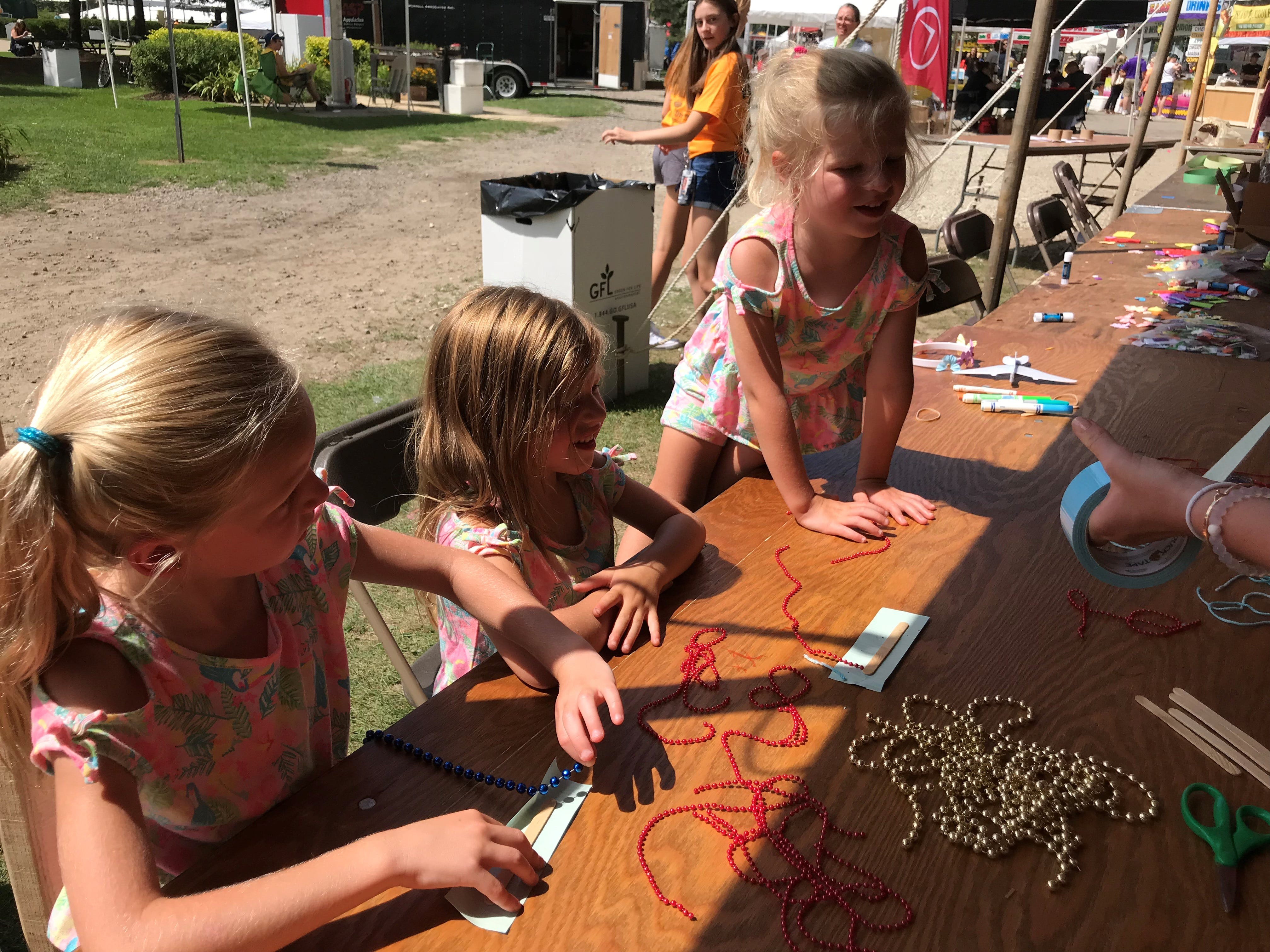 Joslyn Kozub (left), 6, and twin sisters Sophia and Ariel took part in the kids' activities area Friday at Milford Memories.