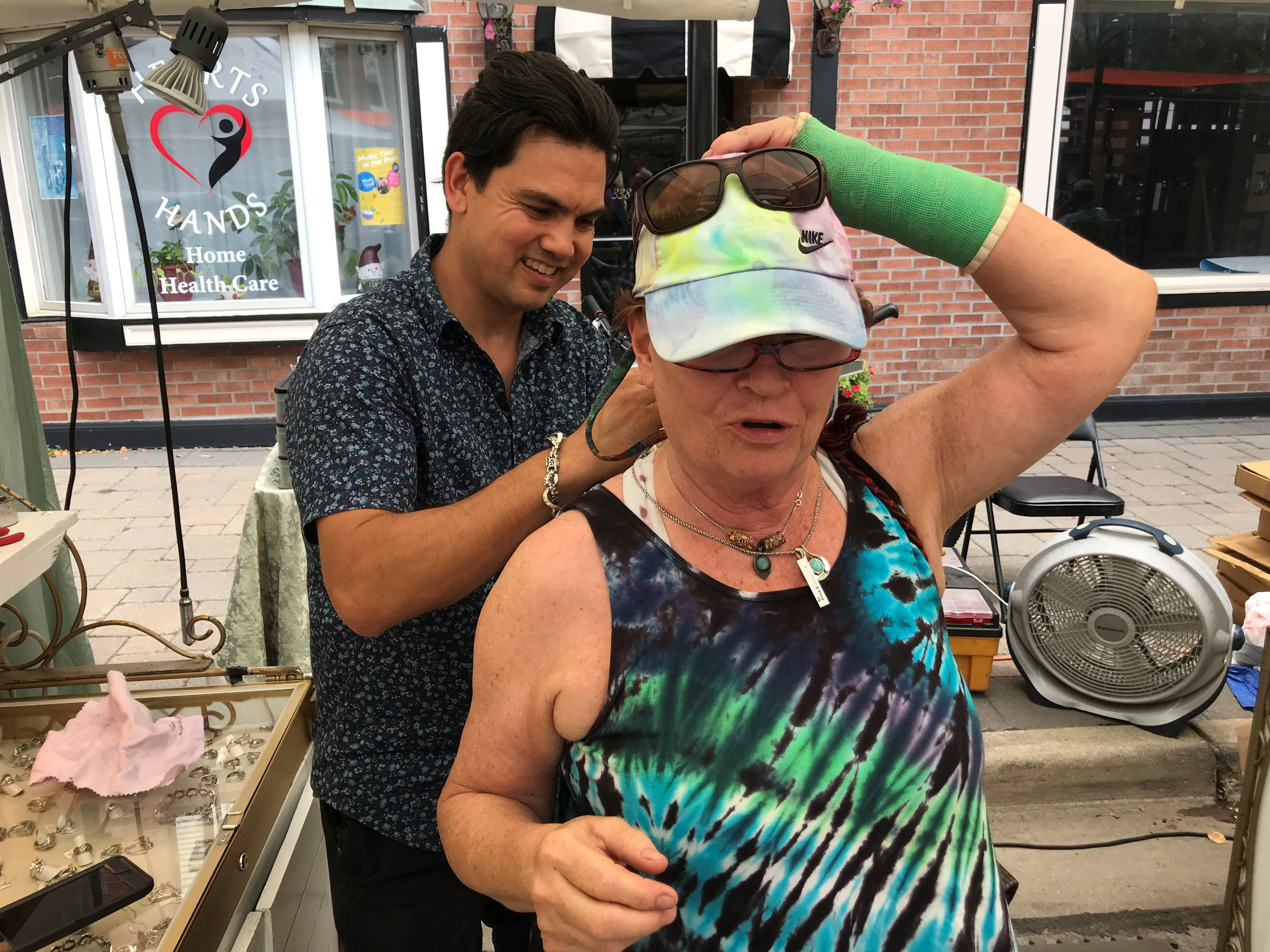 Patti Barkley of Bloomfield Township gets some help with jewelry from Shandor Madjar of Colorado Springs, Colo.