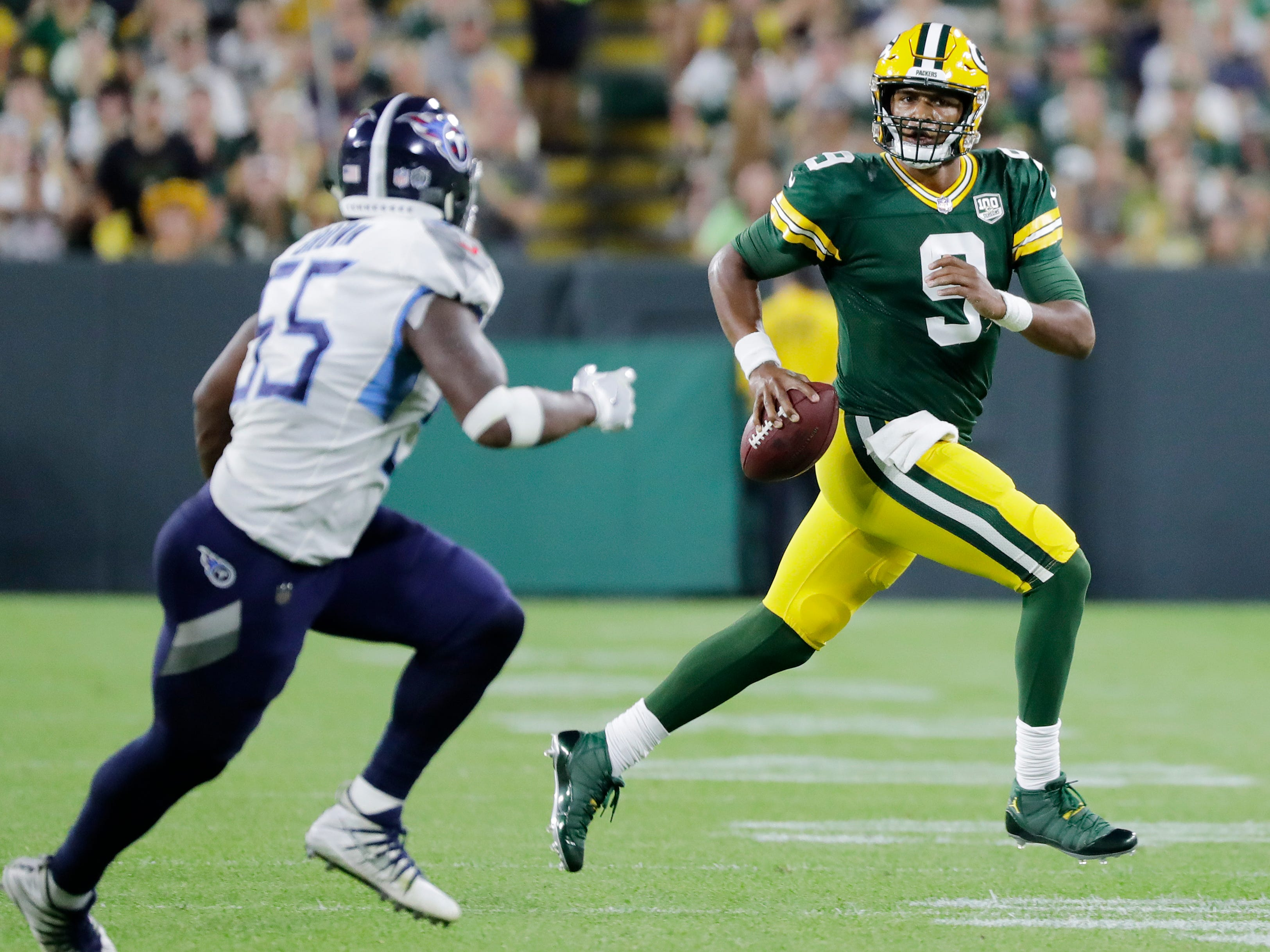 Green Bay Packers quarterback DeShone Kizer (9) scrambles against the Tennessee Titans in the second quarter of a NFL preseason game at Lambeau Field on Thursday, August 9, 2018 in Green Bay, Wis.