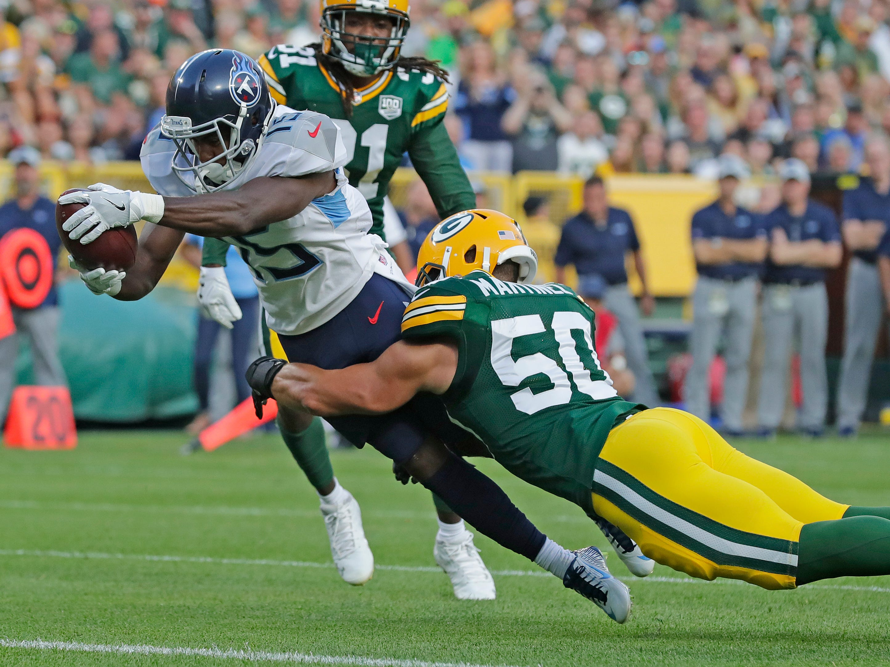Tennessee Titans wide receiver Darius Jennings (15) scores a touchdown against Green Bay Packers linebacker Blake Martinez (50) in the first half of a NFL preseason game at Lambeau Field on Thursday, August 9, 2018 in Green Bay, Wis.