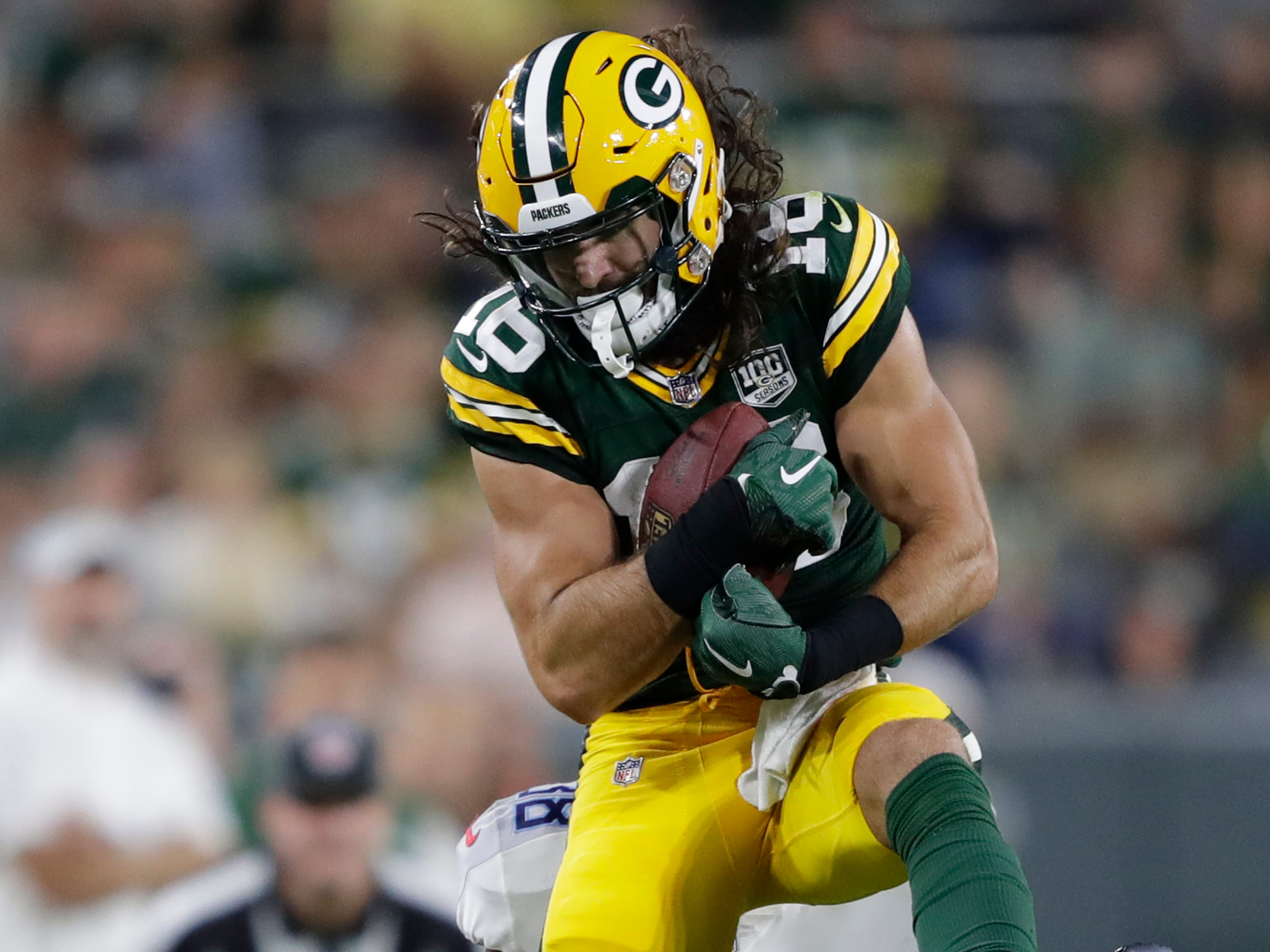 Green Bay Packers wide receiver Jake Kumerow (16) pulls down a reception against Tennessee Titans defensive back Joseph Este (38) during their football game Thursday, August 9, 2018, at Lambeau Field in Green Bay, Wis.