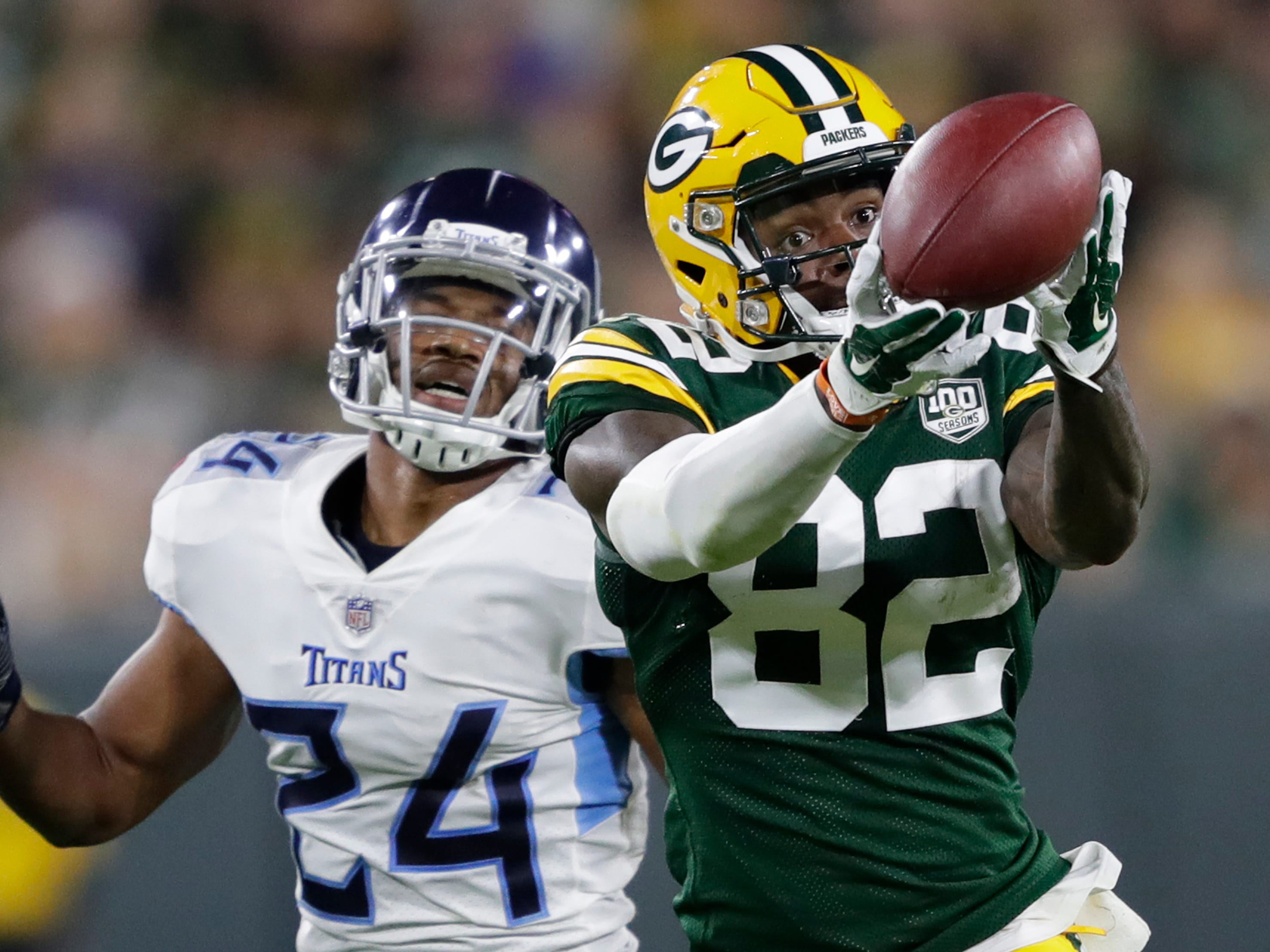 Green Bay Packers wide receiver J'Mon Moore (82) drops a pass against Tennessee Titans defensive back Kalan Reed (24) during their football game Thursday, August 9, 2018, at Lambeau Field in Green Bay, Wis.