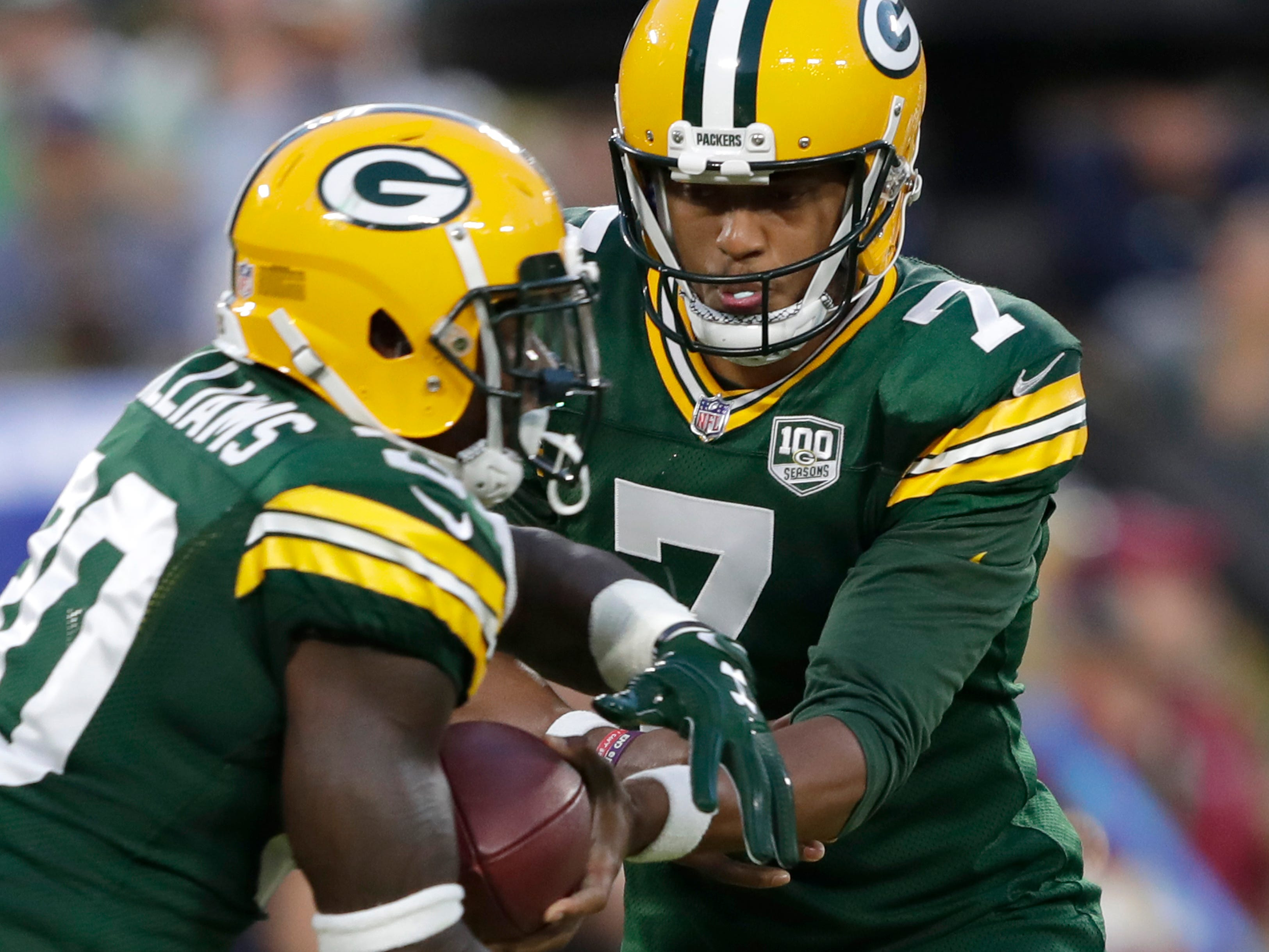 Green Bay Packers quarterback Brett Hundley (7) hands off to Jamaal Williams (30) against the Tennessee Titans during their football game Thursday, August 9, 2018, at Lambeau Field in Green Bay, Wis.