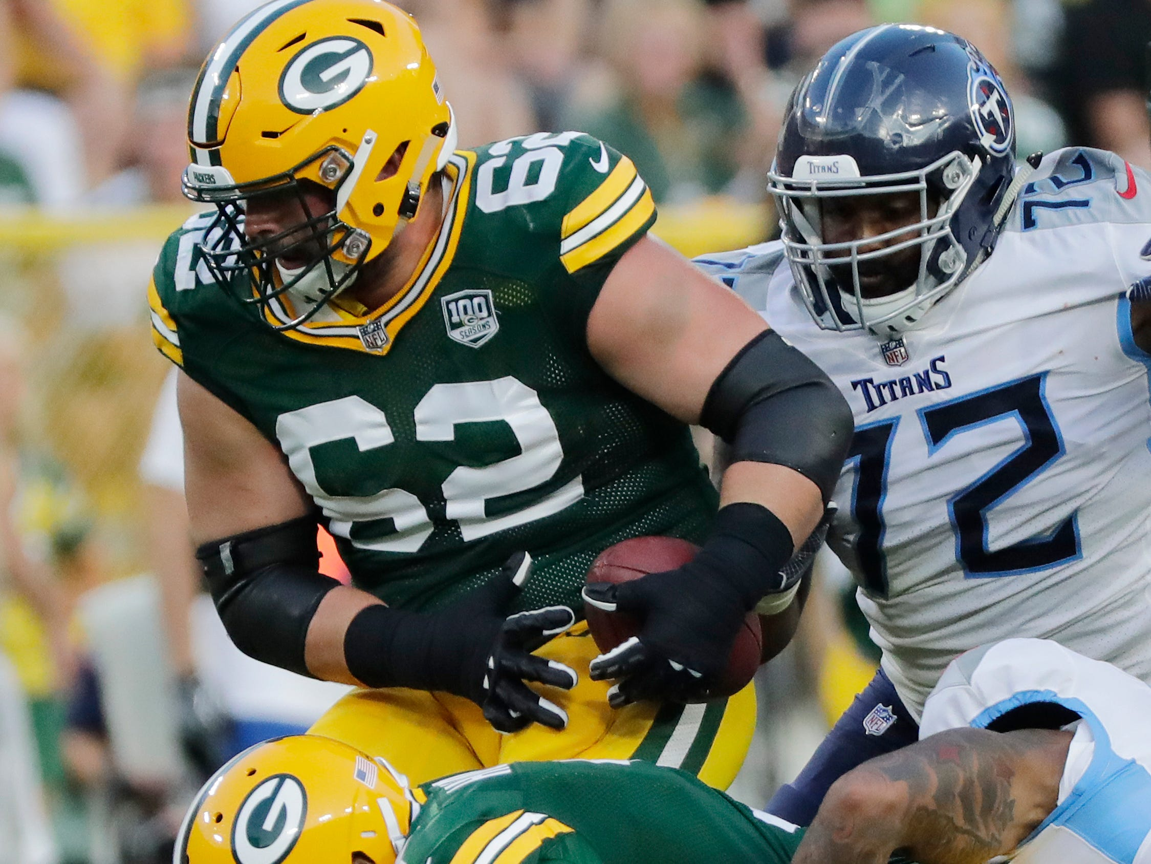 Green Bay Packers offensive guard Lucas Patrick (62) recovers the ball after Green Bay Packers quarterback Brett Hundley (7) fumbled against the Tennessee Titans in the first half of an NFL preseason game at Lambeau Field on Thursday, August 9, 2018 in Green Bay, Wis.