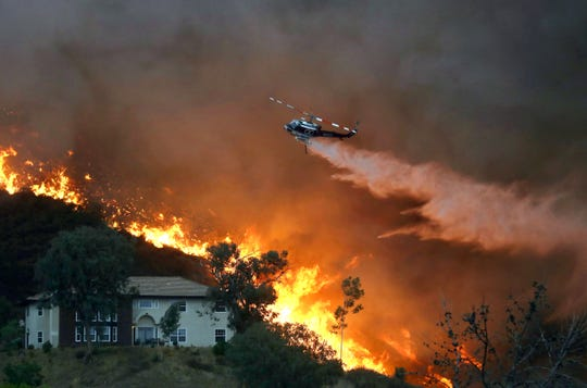 A firefighting helicopter makes a water drop as the Holy Fire burns near homes on Aug. 9 in Lake Elsinore. The fire charred about 23,000 acres in Orange and Riverside counties.