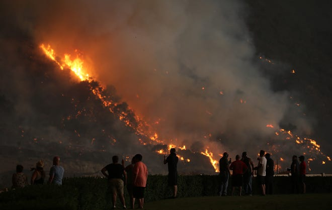 CORONA, CA - AUGUST 09:  People watch as the Holy Fire burns near homes on August 9, 2018 in Corona, California. The fire continues to grow amidst a heat wave and has now burned 10,236 acres while remaining just five percent contained.  (Photo by Mario Tama/Getty Images)