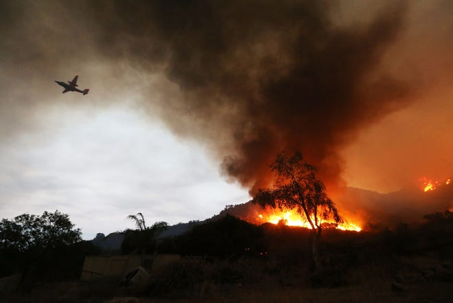 A firefighting aircraft passes above as the Holy Fire burns near homes on August 9, 2018 in Lake Elsinore, California. The fire continues to grow amidst a heat wave and has now burned 10,236 acres while remaining just five percent contained.