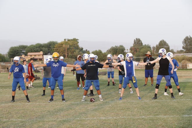 The Conquerors work on offensive sets in practice, now sporting a traditional five- or six-man offensive line. That's because they have moved from an eight-man team to an 11-man team.