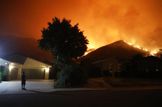 A man stands in a driveway as the Holy Fire burns near homes on August 9, 2018 in Lake Elsinore, California. The fire continues to grow amidst a heat wave and has now burned 10,236 acres while remaining just five percent contained.