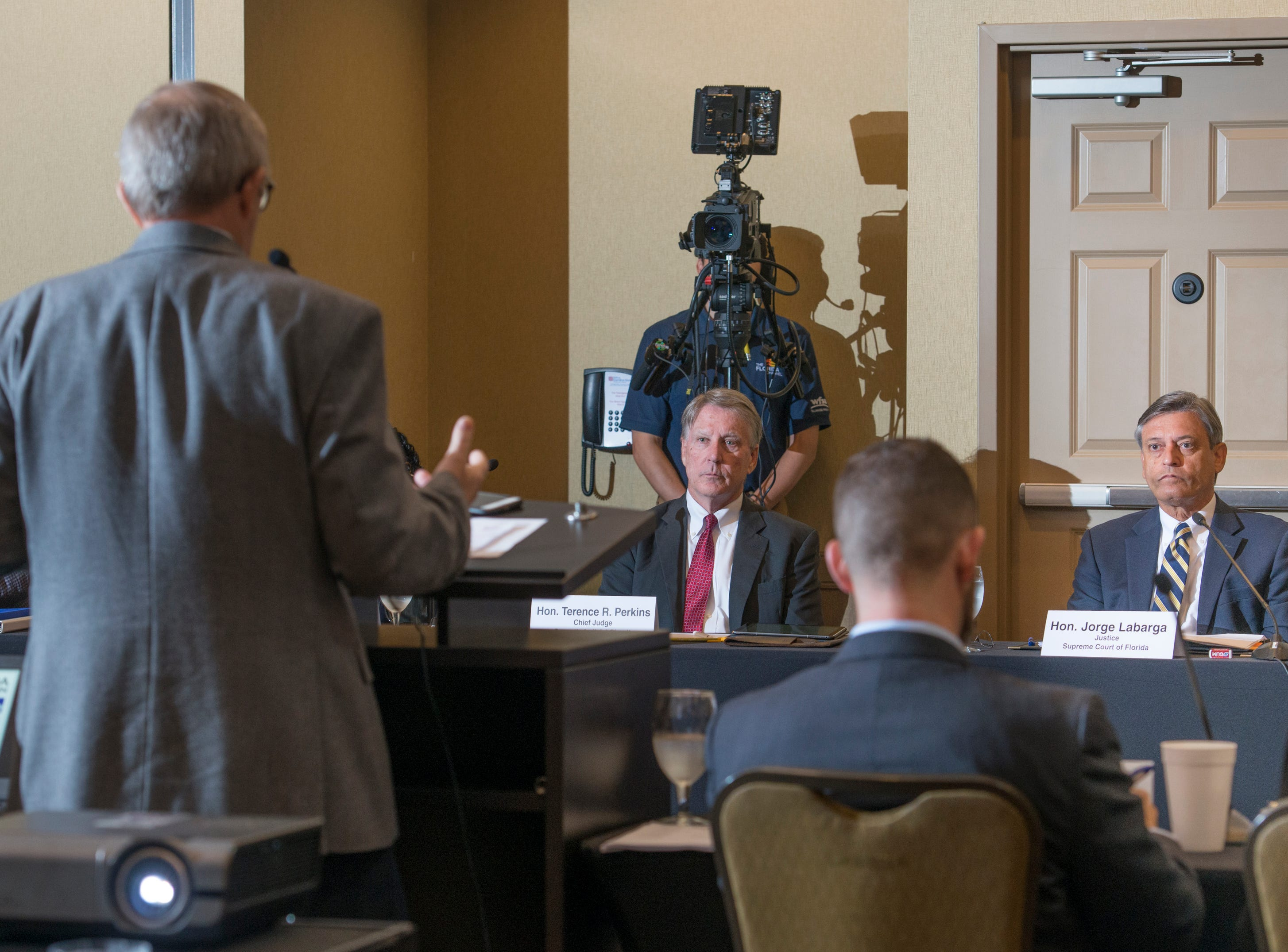 Seventh Judicial Circuit chief judge Terence Perkins, left, and Supreme Court of Florida justice Jorge Labarga listen to Florida Veterans Foundation president Dennis Baker speak as the Florida Commission on Access to Civil Justice discusses veterans issues at the Hilton Garden Inn in Pensacola on Friday, August 10, 2018.