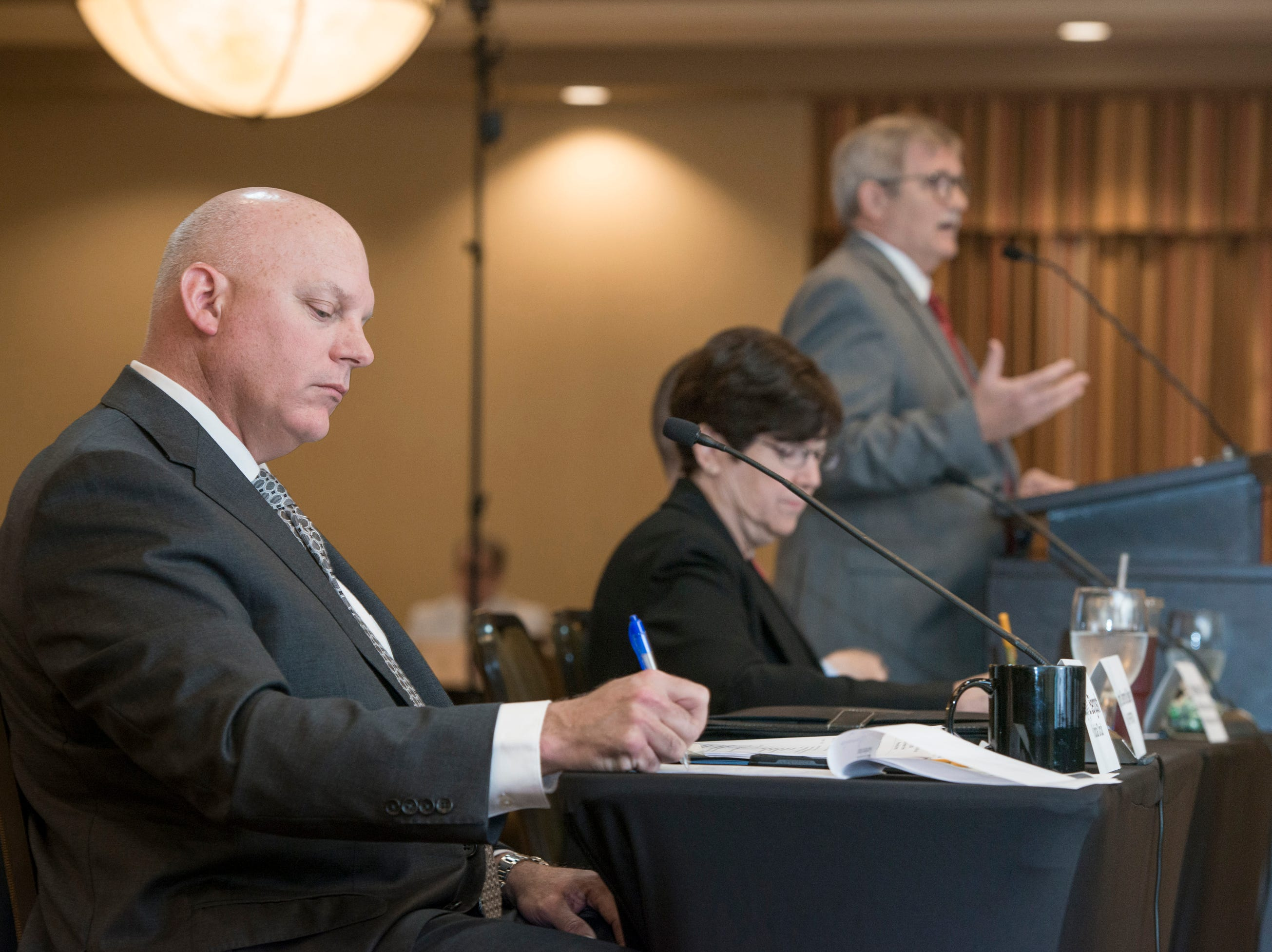 First Judicial Circuit judge Gary Bergosh, left, takes notes as Florida Veterans Foundation president Dennis Baker speaks during the Florida Commission on Access to Civil Justice discussion of veterans issues at the Hilton Garden Inn in Pensacola on Friday, August 10, 2018.