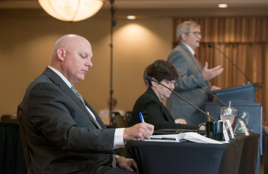 First Circuit Court Judge Gary Bergosh, left, takes notes Friday as Florida Veterans Foundation President Dennis Baker speaks during the Florida Commission on Access to Civil Justice's discussion of veterans issues at the Hilton Garden Inn in Pensacola.