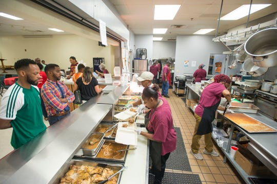 Workers prepare and serve lunch at the All in One Kitchen Ministry at Englewood Baptist Church in Pensacola on Friday, August 10, 2018.